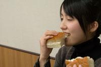 牛乳パンをかじる女性