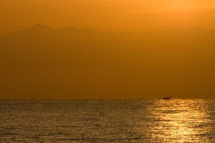 朝日に染まる漁船と山々