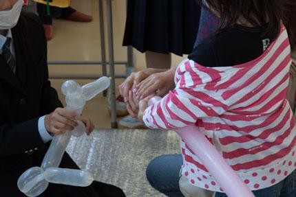 小さい子に風船で人形の作り方を教えていたり
