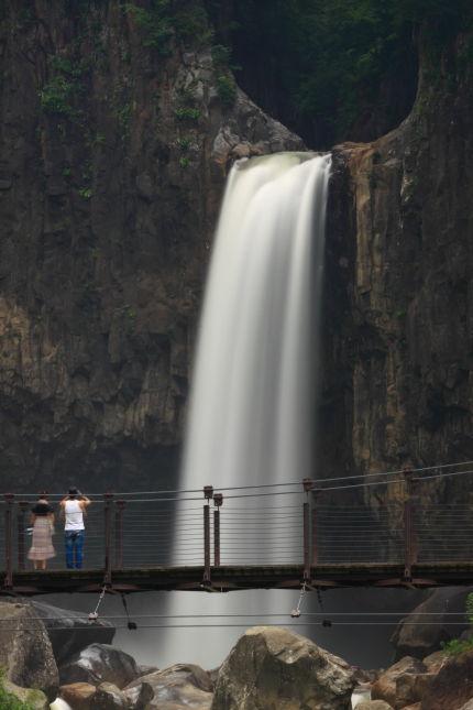 吊り橋で滝を眺めるカップル
