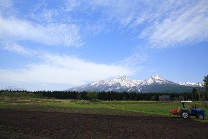 耕された畑と妙高山