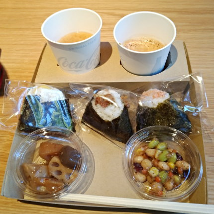 紙トレーに紙コップ2つと箸、2種類の総菜(この日は、大豆サラダと煮物)、おにぎり