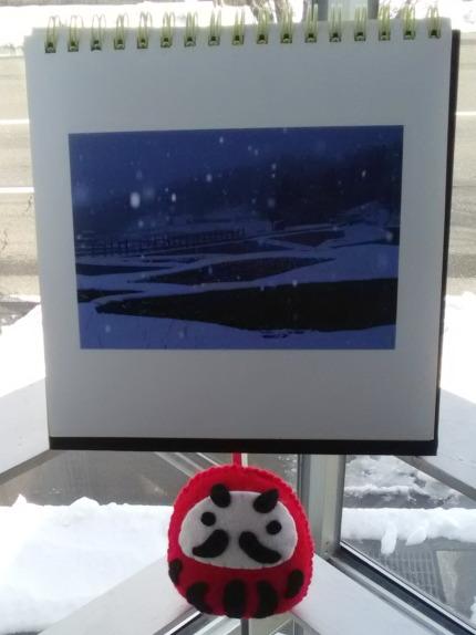 雪の写真とだるまの正月飾り